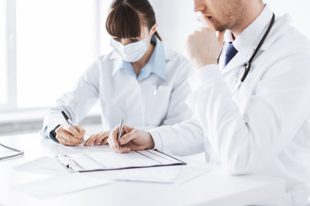 picture of doctor and nurse writing prescription paper photo