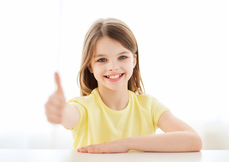 pre approval: home, education, happiness and people concept - beautiful little girl at home showing thumbs up