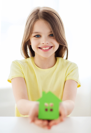 home and family concept - little girl holding green paper house photo