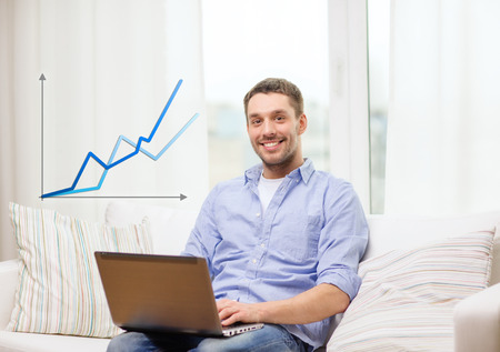 business, technology and e-learning concept - smiling man working with laptop at home photo