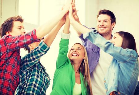 amistad: estudiantes felices dando de alta cinco en la escuela - educación y concepto de la amistad