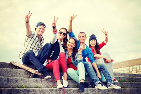 summer holidays and teenage concept - group of smiling teenagers hanging outside and showing v-sing photo
