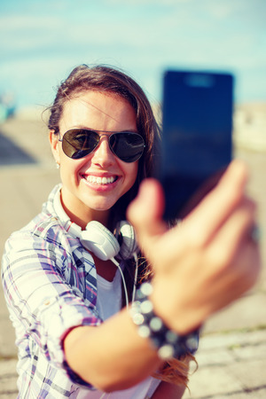 holidays and tourism concept - smiling teenage girl taking picture with smartphone camera outdoors photo