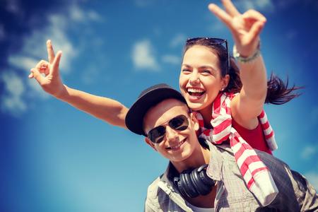 pareja de adolescentes: vacaciones de verano, las relaciones y el concepto de adolescencia - adolescentes sonrientes en gafas de sol que se divierten afuera y mostrando la v-muestra Foto de archivo