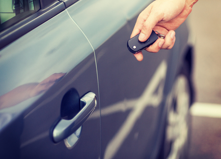hand key: transportation and ownership concept - man with car key outside