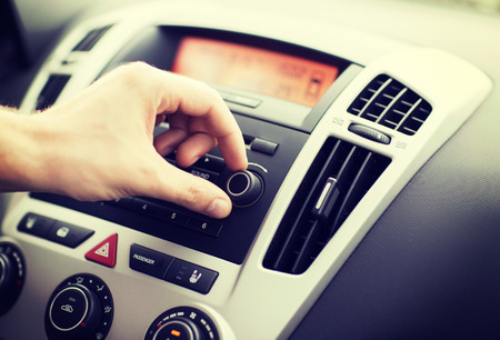 car audio: transportation and vehicle concept - man using car audio stereo system Stock Photo