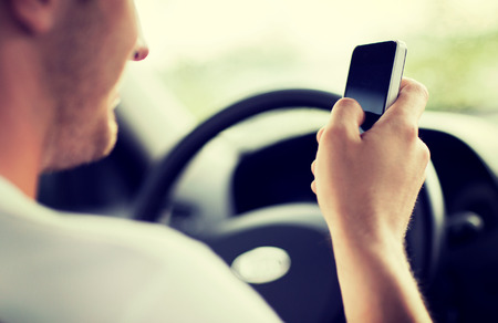 transportation and vehicle concept - man using phone while driving the car photo