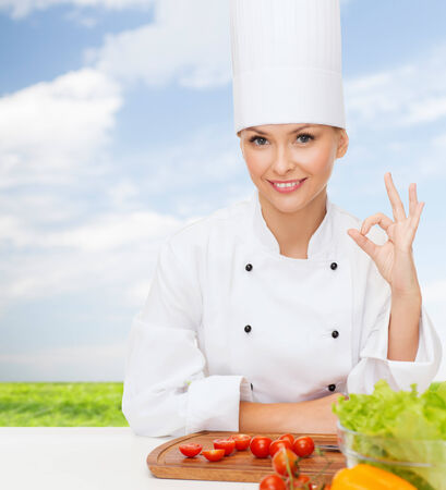 cooking and food concept - smiling female chef with vegetables showing ok sign photo