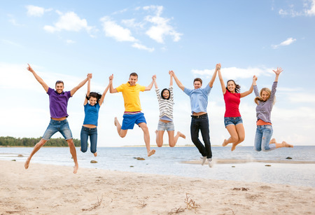 summer, holidays, vacation, happy people concept - group of friends jumping on the beach Stock Photo