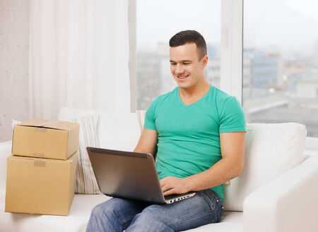 technology, home and lifestyle concept - smiling man with laptop and cardboard boxes at home photo