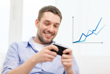 home, technology and internet concept - smiling man with smartphone sitting on couch at home photo