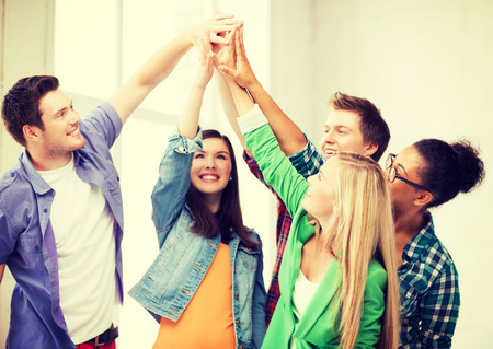 education and friendship concept - happy students giving high five at school photo