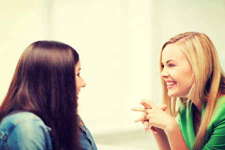 education concept - student girls gossiping at school photo