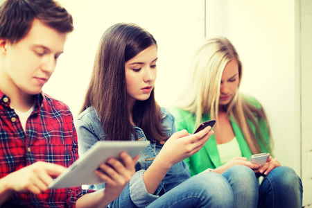 education concept - students looking into phones and tablet pc at school photo