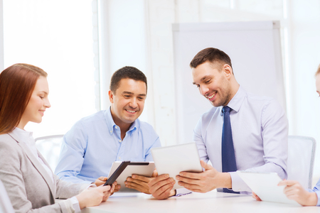 group goals: business and office concept - smiling business team working with tablet pc computers in office Stock Photo