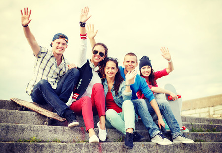 summer holidays and teenage concept - group of smiling teenagers hanging outside and waving hands photo