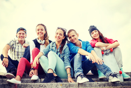 chilling out: summer holidays and teenage concept - group of smiling teenagers hanging outside