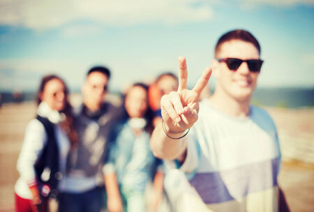 back up: summer holidays and teenage concept - close up of male hand showing v-sign with fingers with friends on the back Stock Photo