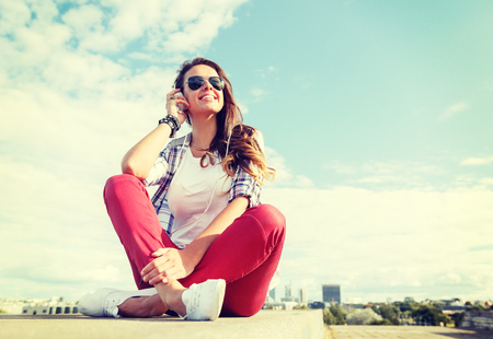 nice girl: summer holidays and teenage concept - smiling teenage girl in sunglasses with headphones outdoors