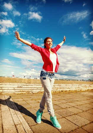 sport, dancing and urban culture concept - beautiful dancing girl in movement with raised hands photo