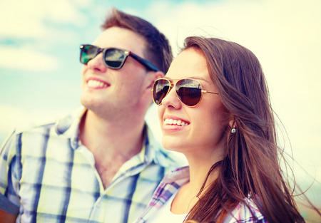chilling out: summer holidays, relationships and teenage concept - smiling teenagers in sunglasses having fun outside