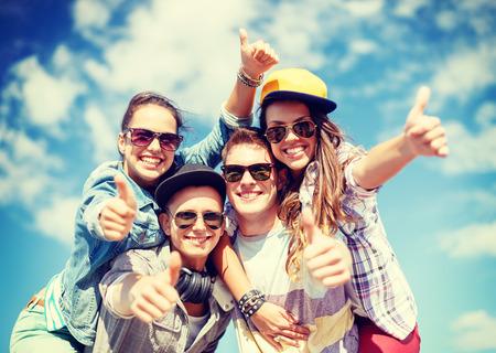 adolescente: vacaciones de verano y concepto de adolescentes - grupo de adolescentes sonrientes en gafas de sol que cuelga afuera y mostrando los pulgares para arriba