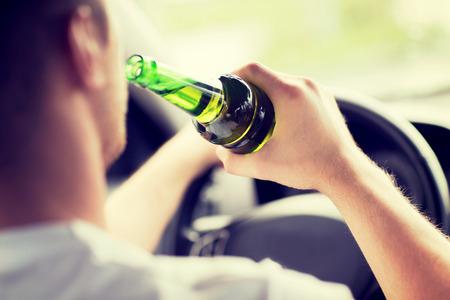 교통 및 차량 개념 - 자동차를 운전하는 동안 알코올을 마시는 사람