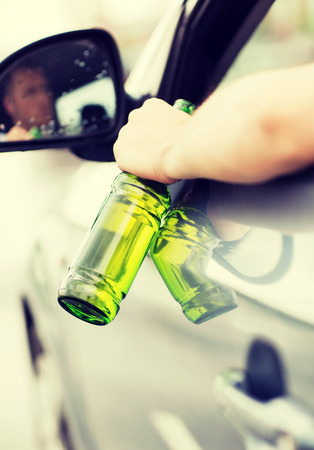 drinking driving: transportation and vehicle concept - man drinking alcohol while driving the car