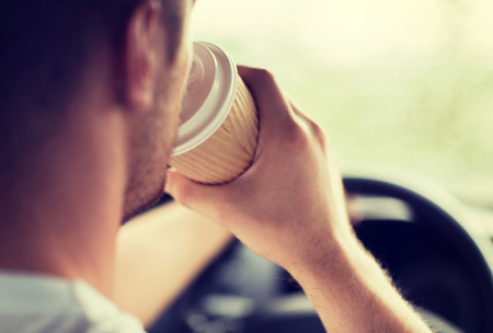 early morning: transportation and vehicle concept - man drinking coffee while driving the car