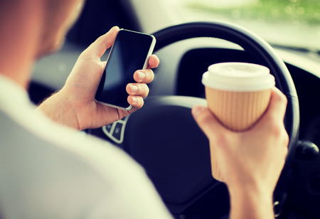 drinking and driving: transportation and vehicle concept - man drinking coffee and using phone while driving the car