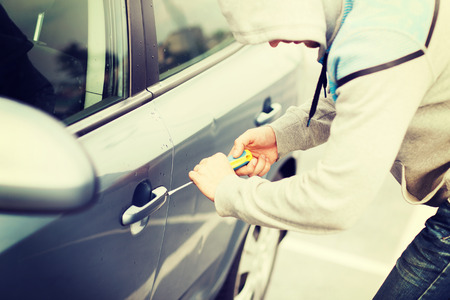 vervoer, misdaad en eigendom concept - dief breken van de auto-lock