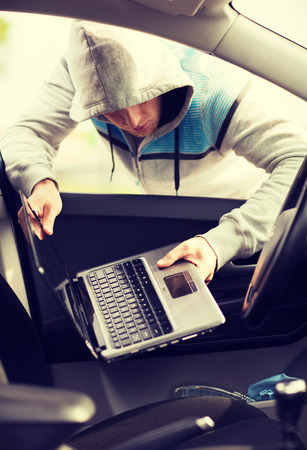 breakin: transportation, crime and ownership concept - thief stealing laptop from the car Stock Photo