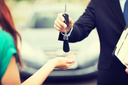 交通機関、所有権概念 - 顧客と外の車のキーを持つセールスマン