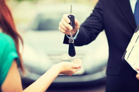 unlocking: transportation and ownership concept - customer and salesman with car key outside