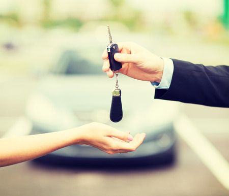 transportation and ownership concept - customer and salesman with car key outside photo