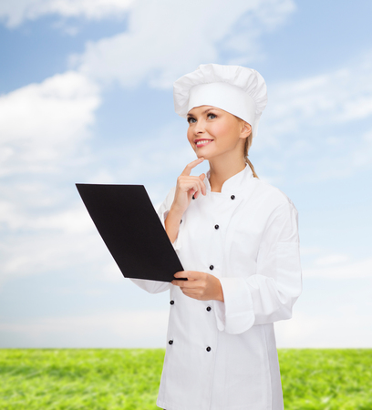 deciding: cooking, advertisement and food concept - smiling female chef, cook or baker with blank black menu paper