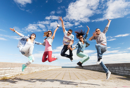 summer, sport, dancing and teenage lifestyle concept - group of teenagers jumping 版權商用圖片