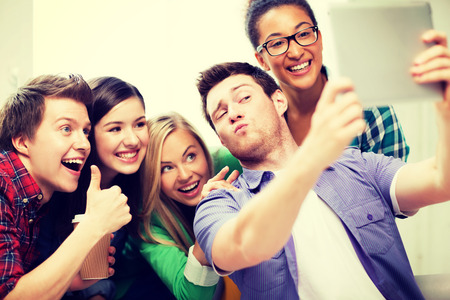 technology concept - group of students making picture with tablet pc Stock Photo