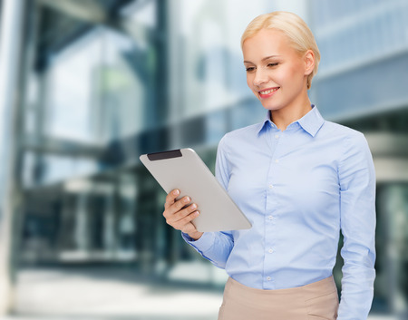 business, internet and technology concept - smiling woman looking at tablet pc computer photo