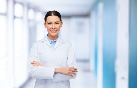 healthcare and medicine concept - smiling female doctor with crossed arms at hospital