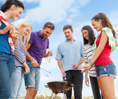 summer holidays, food and drink, happy people concept - group of friends making barbecue on the beach photo