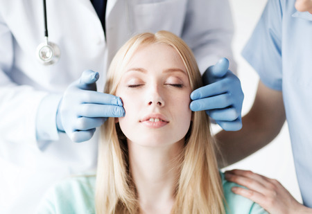 healthcare, medical and plastic surgery concept - plastic surgeon and nurse with patient in hospital photo