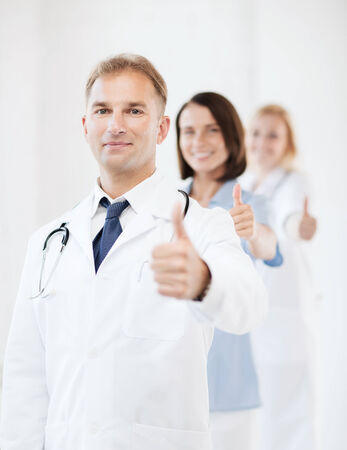 doctor appointment: healthcare and medical concept - male doctor with stethoscope and colleagues showing thumbs up