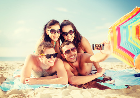 beaches: summer, holidays, vacation, technology and happiness concept - group of smiling people in sunglasses taking picture with smartphone on beach