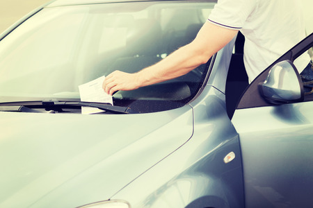 transportation and vehicle concept - parking ticket on car windscreen photo