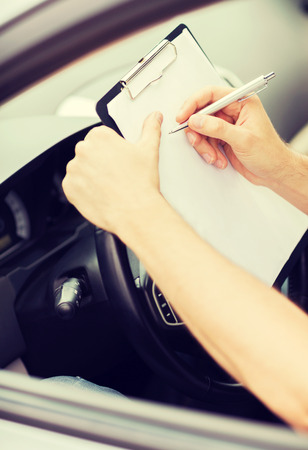 transportation and ownership concept - man with car documents photo