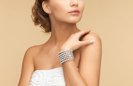 earrings: beautiful bride wearing pearl earrings and bracelet