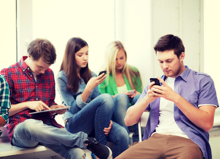 smartphone addiction: education and internet concept - students looking into phones and tablet pc