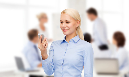 business, technology, internet and education concept - friendly young smiling businesswoman with smartphone photo