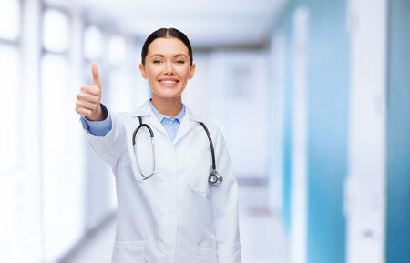 healthcare and medicine concept - smiling female doctor with stethoscope showing thumbs up photo